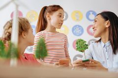 Cute schoolgirl chatting with her teacher about ecology. Informative chat. Adorable teenage girl chatting with her teacher and classmate about ecology and Royalty Free Stock Photos