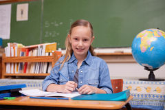 Cute schoolgirl doing classwork Stock Image