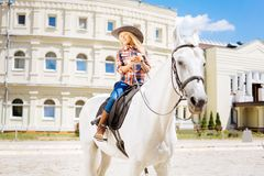 Cute schoolgirl fond of equestrianism riding horse on weekend. Schoolgirl and equestrianism. Cute schoolgirl wearing stylish cowboy hat fond of equestrianism stock images