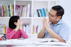 Cute schoolgirl getting applause from her teacher. Picture of cute schoolgirl finishing homework and getting applause from her teacher in the library royalty free stock images