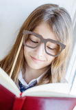 Cute schoolgirl in glasses holding a book Royalty Free Stock Image
