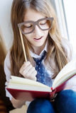 Cute schoolgirl in glasses holding a book Royalty Free Stock Photo
