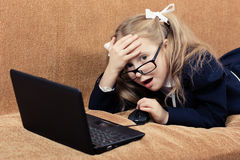 Child with a laptop in shock. Cute schoolgirl with glasses and laptop in a state of shock Royalty Free Stock Images