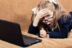 Child with a laptop in shock. Cute schoolgirl with glasses and laptop in a state of shock Royalty Free Stock Photography