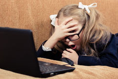 Child with a laptop in shock. Cute schoolgirl with glasses and laptop in a state of shock Royalty Free Stock Photos