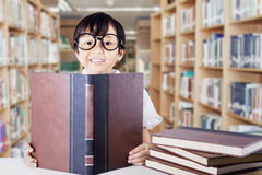 Cute schoolgirl with glasses reading books Royalty Free Stock Photo