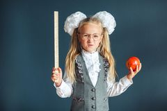 Cute schoolgirl with glasses and red Apple in hand looking like a strict teacher raised her pointer to draw attention. Educational. Concept. School concept royalty free stock photo