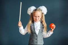 Cute schoolgirl with glasses and red Apple in hand looking like a strict teacher raised her pointer to draw attention. Educational. Cute schoolgirl with red royalty free stock photography