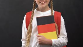 Cute schoolgirl holding book with German flag, language studying, education. Stock footage stock footage