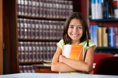 Cute Schoolgirl Holding Book While Sitting In Royalty Free Stock Images