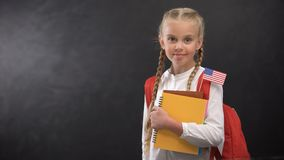 Cute schoolgirl holding books with tiny USA flag ready to learn foreign language. Stock footage stock footage