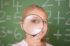 Cute schoolgirl looking through a magnifying glass stock photography
