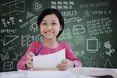 Cute schoolgirl making notes on a paper Stock Photos