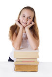 Cute schoolgirl on pile of books Royalty Free Stock Photos