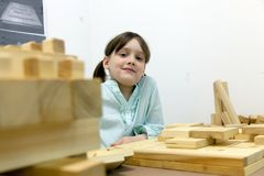 Cute schoolgirl playing with wooden puzzles. Stock Photo