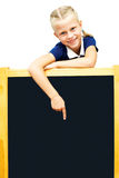 Cute schoolgirl points to a blackboard. Stock Images