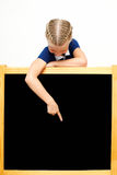 Cute schoolgirl points to a blackboard. Advertising. Isolated on Royalty Free Stock Image