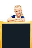 Cute schoolgirl points to a blackboard. Advertising. Isolated on Stock Images