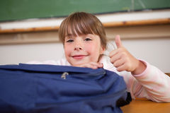 Cute schoolgirl posing with a bag and the thumb up. In a classroom Stock Images