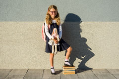 A cute schoolgirl of primary school is smiling with a toy in her Royalty Free Stock Photography