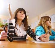 Cute schoolgirl is raising her hand Stock Photography