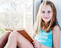 Cute schoolgirl reading while sitting on the window royalty free stock image