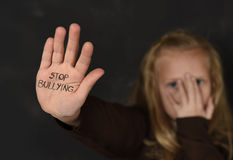Cute schoolgirl scared sad asking for help showing hands with stop bullying text written on her palm Royalty Free Stock Photo