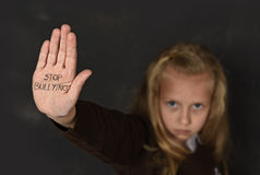 Cute schoolgirl scared sad asking for help showing hands with stop bullying text written on her palm Royalty Free Stock Photography