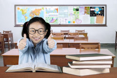 Cute schoolgirl showing ok sign in classroom Royalty Free Stock Photos