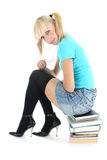 Cute schoolgirl sitting on stacked books Stock Photography
