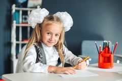 Cute girl sitting at table and drawing. Portrait of a beautiful girl in the classroom. Schoolgirl with white bows sitting at the stock photo