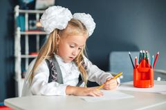 Cute schoolgirl sitting at table and drawing. Portrait of a beautiful girl in the classroom. Little schoolgirl with white bows royalty free stock photos