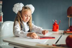Cute schoolgirl sitting at table and drawing. Portrait of a beautiful girl in the classroom. Little schoolgirl with white bows royalty free stock photography