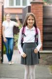 Cute schoolgirl standing in front of house. Mother waving standi. Portrait of cute schoolgirl standing in front of house. Mother waving standing in doorway and Stock Images