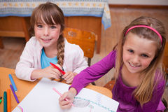 Cute schoolgirls drawing in a coloring book Royalty Free Stock Photo