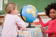 Cute schoolgirls looking at a globe. In a classroom Royalty Free Stock Photos