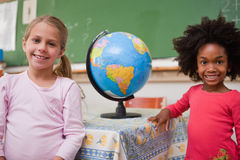 Cute schoolgirls posing with a globe. In a classroom Royalty Free Stock Photography