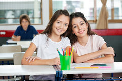Cute Schoolgirls Sitting Together At Desk Royalty Free Stock Photo