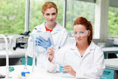 Cute science students doing an experiment Royalty Free Stock Image