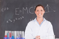 Cute scientist standing in front of a blackboard royalty free stock photo