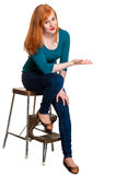 Cute seated redhead, indicating space for text Royalty Free Stock Image