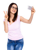 The cute selfie. Cropped studio shot of a young woman  taking a selfie with an smart phone Royalty Free Stock Image