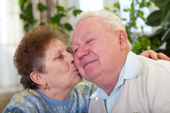 Cute senior couple kissing. Picture of a cute elderly couple kissing at home Stock Photo