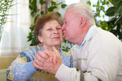 Cute senior couple kissing. Picture of a cute elderly couple kissing at home Royalty Free Stock Photos