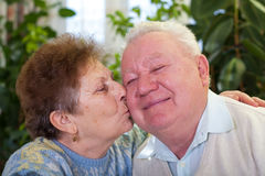 Cute senior couple kissing. Picture of a cute elderly couple kissing at home Stock Photos