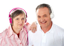 Cute senior couple listening to music together. Portrait of a cute senior couple listening to music together against white background Royalty Free Stock Photos