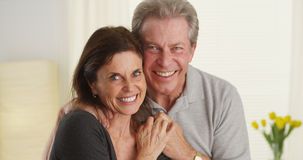 Cute senior couple smiling and looking at camera. In their home royalty free stock images