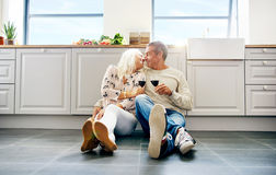 Cute senior husband and wife kissing. Each other while seated on floor in kitchen with bright windows and large cabinets Royalty Free Stock Photo