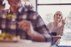 Cute senior lady holding hand up and looking aside. Help me somebody. Cute senior pleasant lady spending time in the cafe holding hand up and looking aside stock photo