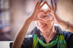 Senior woman making a heart shape, cute and lovely. Cute senior old woman making a heart shape with her hands and fingers royalty free stock photography